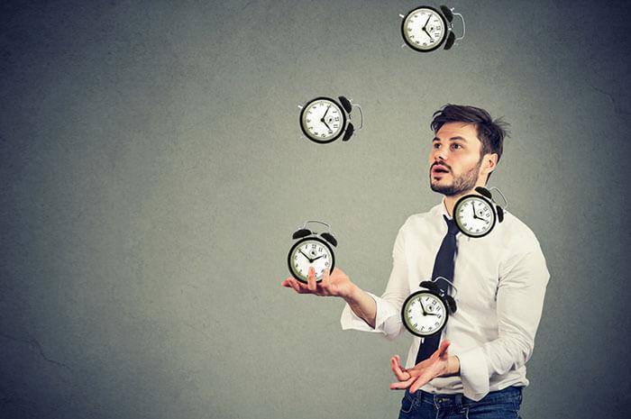 man juggling clocks