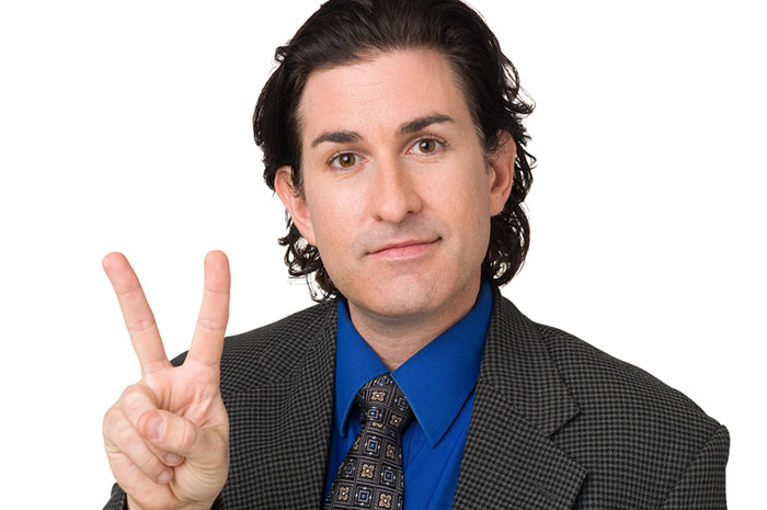 man holding up peace sign